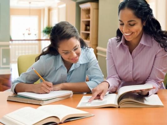 Hispanic mother helping daughter with homework